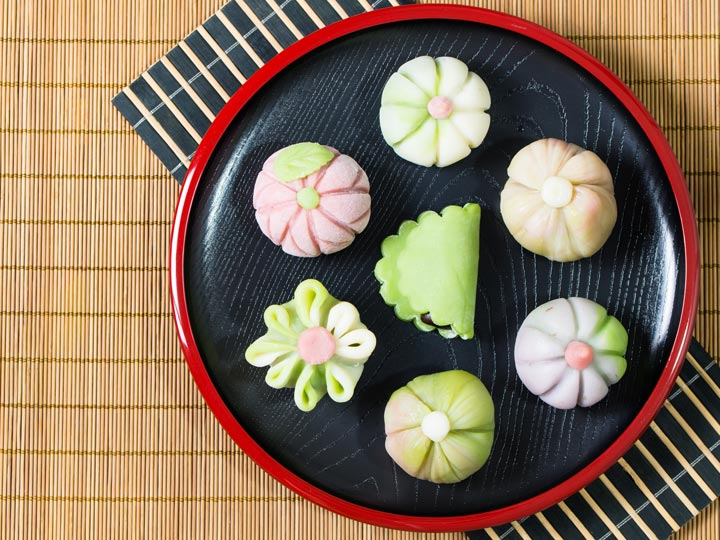 Pink and green flower shaped wagashi on plate with bamboo mat