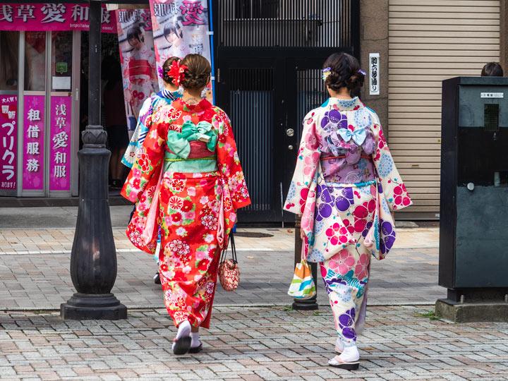 Two girls wearing colorful printed yukata walking away down the street