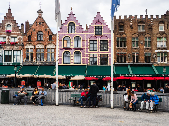 Benches in front of pink and brown old buildings lining market square in Bruges in winter