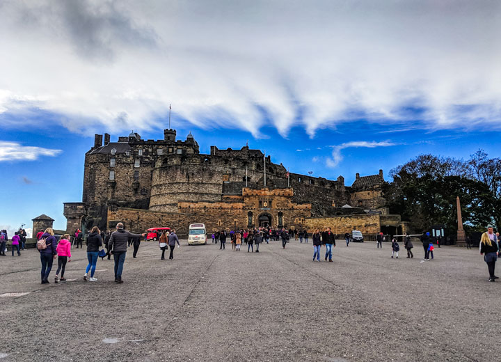Front view of Edinburgh Castle with tourists under partly cloudy sky