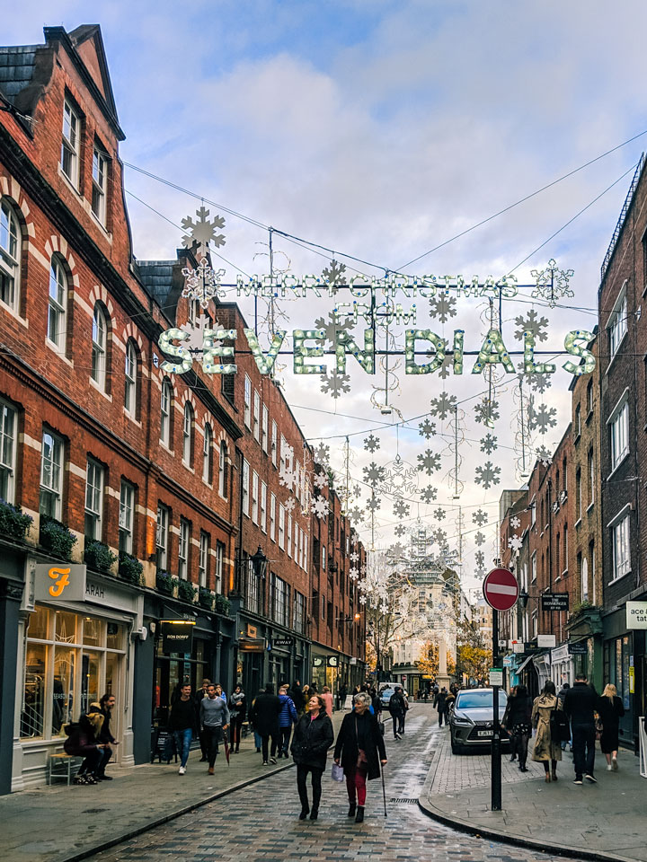 Shoppers walking down illuminated Seven Dials street in London, an excellent choice for winter breaks in Europe