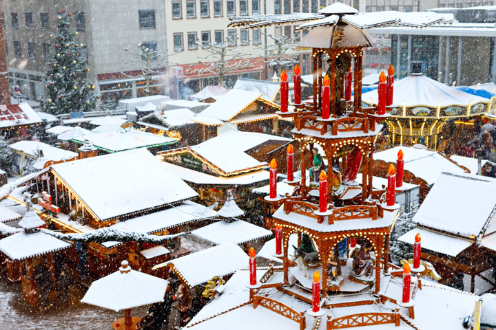 Snow-covered stalls and candle display at Christmas Market in Nuremberg, a popular winter city break in Europe