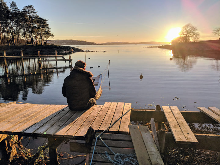 One person sitting on wooden pier overlooking water at sunrise during winter in Oslo Norway