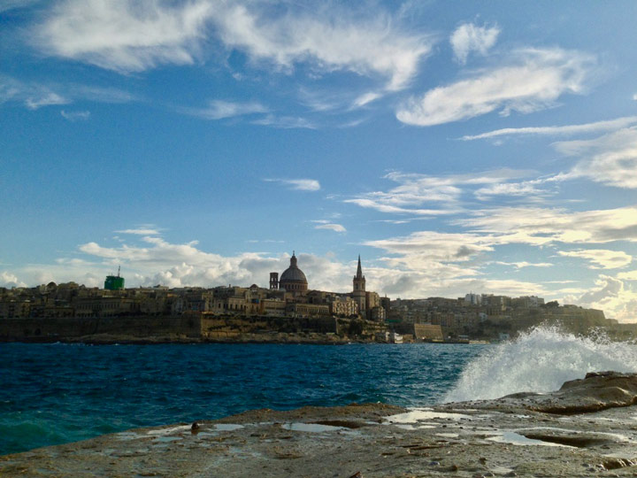 View of Valletta across water with crashing waves on sunny day