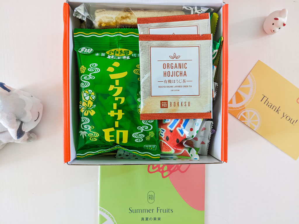 Interior view of Bokksu snack box with organic hojicha packages and lemon cracker snacks on top.
