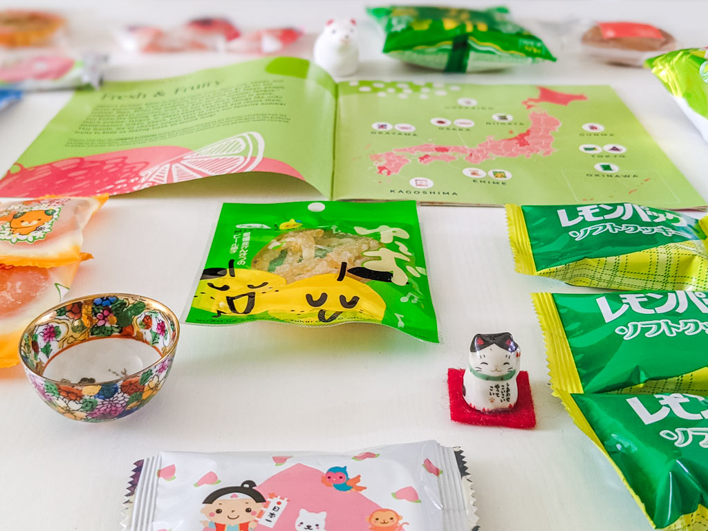 Closeup of lemon peel candy package on table, with map of Japan, cat figurine, and cookie packages  surrounding.