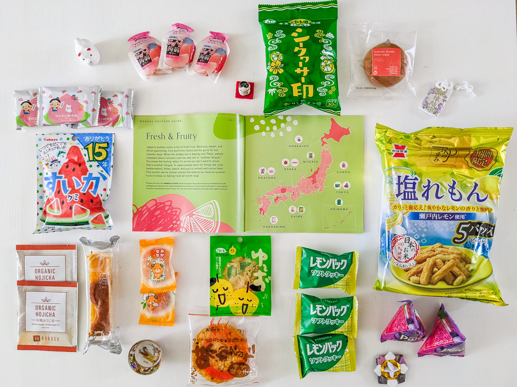 Flat lay of 2021 Bokksu review snack packages found in Summer Fruits box, including rice crackers, orange mochi, and watermelon gummies.