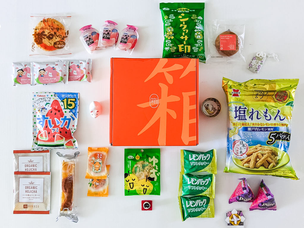 Flat lay of various Japanese snack packages on white table, with orange 2021 Bokksu review box in center.