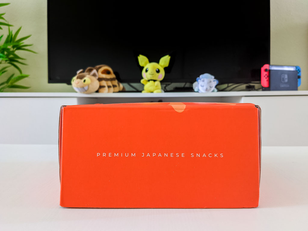 """Closed orange 2021 Bokksu review box on white table, with text """"Premium Japanese Snacks"""" written on front."""
