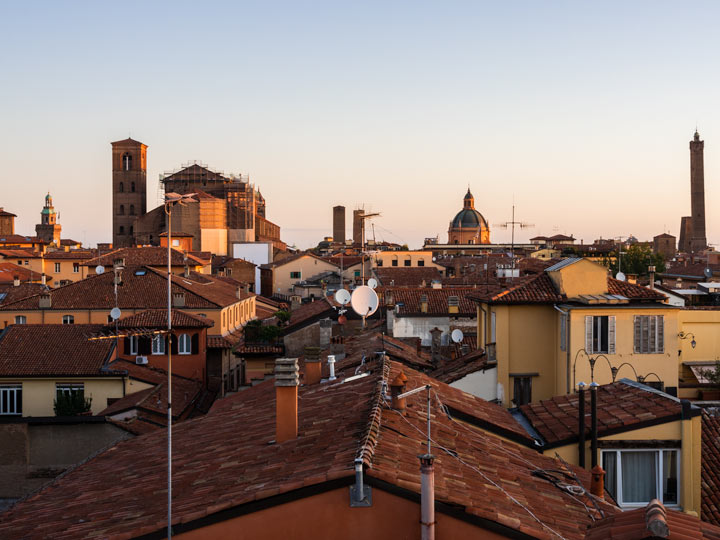 Sunrise over rooftops and skyline of Bologna city center