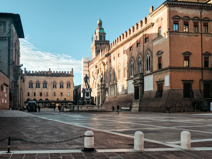 Blue sky morning at Piazza Del Nettuno in Bologna with Neptune Fountain and old palazzo facades