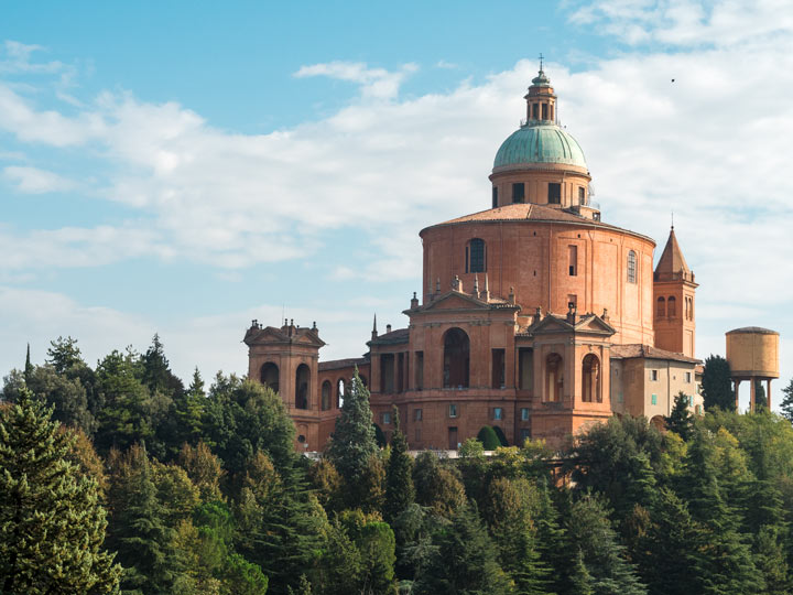 View of Sanctuary of the Madonna di San Luca with trees and blue sky, a popular Bologna sightseeing spot