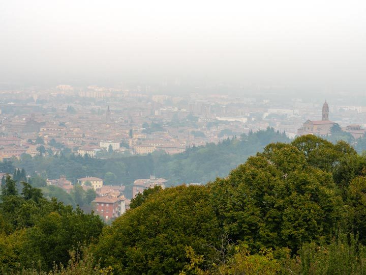 Hazy city view from top of Villa Ghigi Park, a popular Bologna sightseeing spot for panoramic views