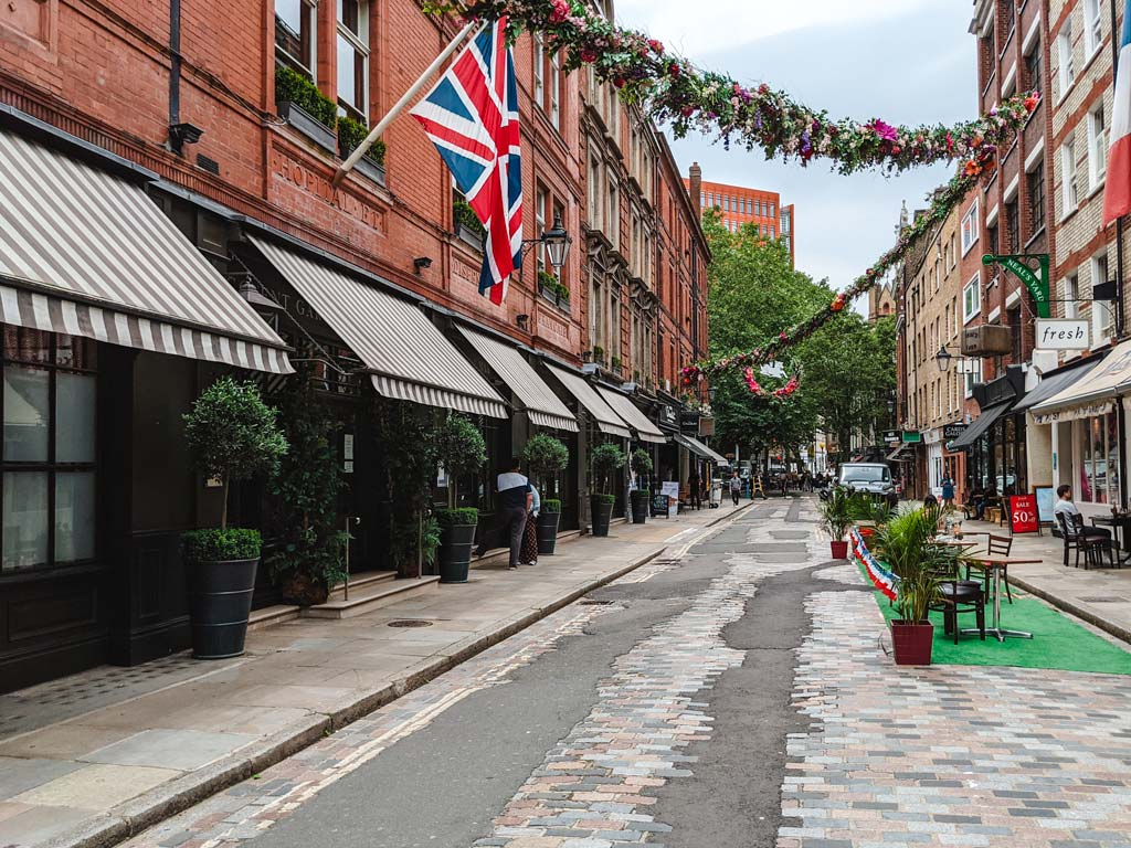 British street with union jack flag and garland hanging from buildings.