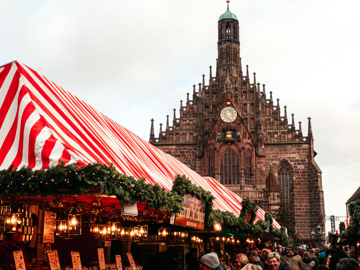 Nuremberg Christmas market red and white striped roof with cathedral in distance