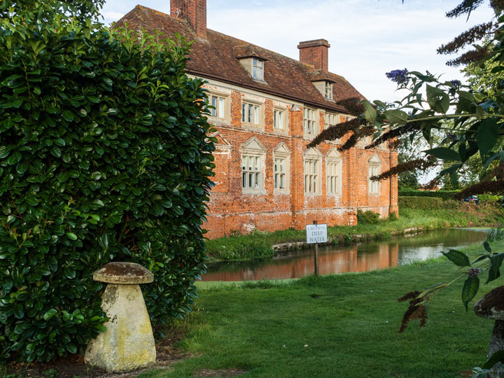 Old UK brick estate house with pond and green bushes in foreground