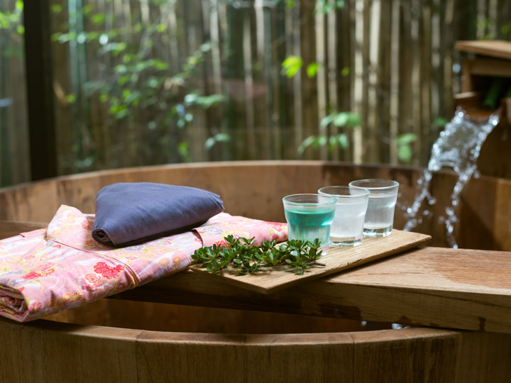 Atami wooden onsen tub with pink yukata and drinks on serving board