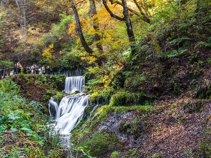 Shiraito Falls stream with autumn leaves in Karuizawa Japan
