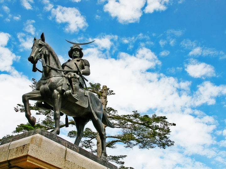 Masamune mounted on horse statue against partly cloudy sky