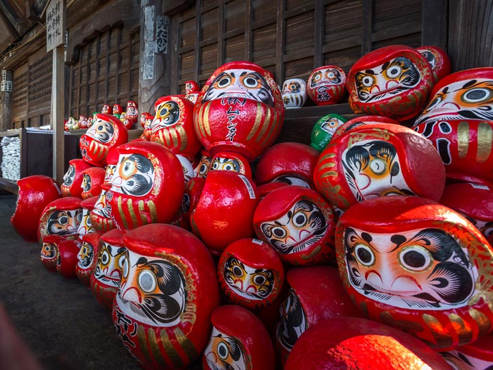 Red daruma figures stacked up at Jiganin temple in Takasaki