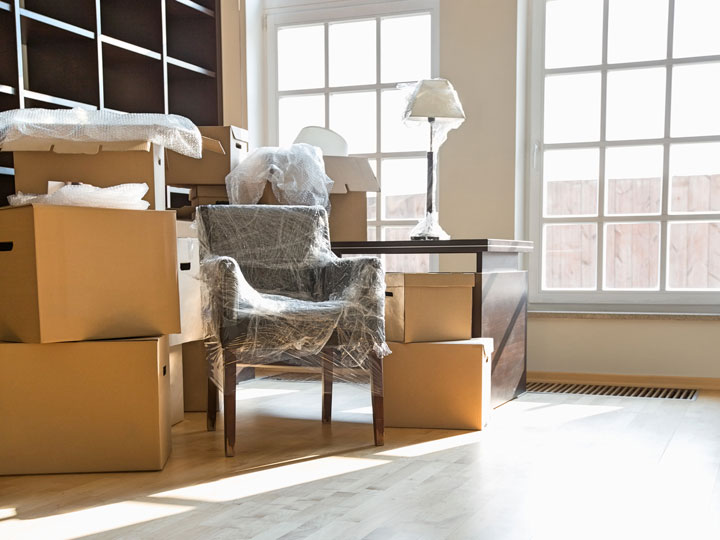 Living room with cardboard boxes stacked up and chair wrapped in plastic