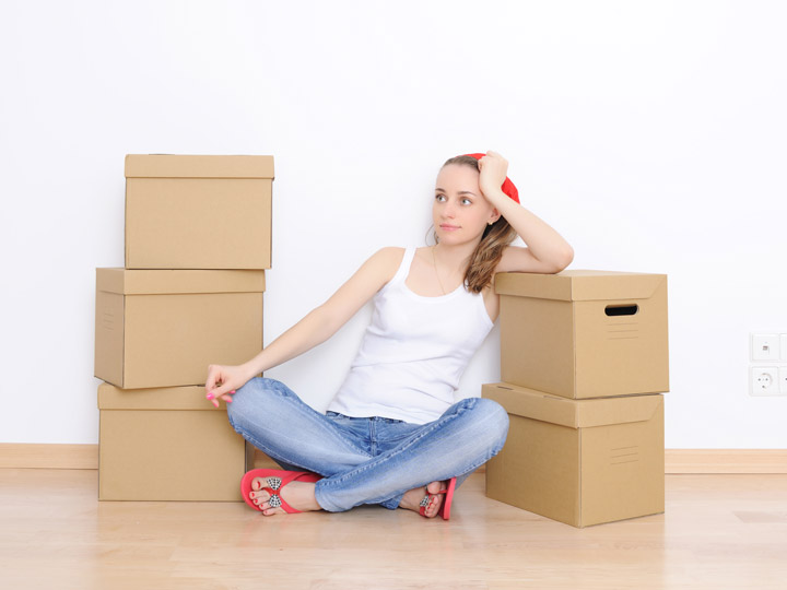 Tired girl sitting on floor with 5 moving boxes, thinking about difficulties of moving to a foreign country