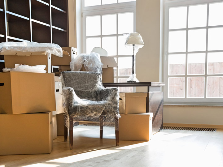 Bright room with cardboard boxes and chair wrapped in plastic for moving