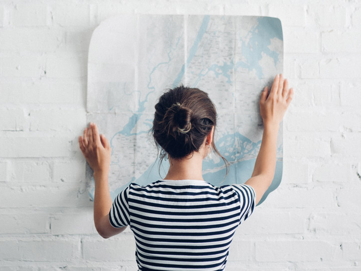 Girl in striped shirt holding map against white brick wall