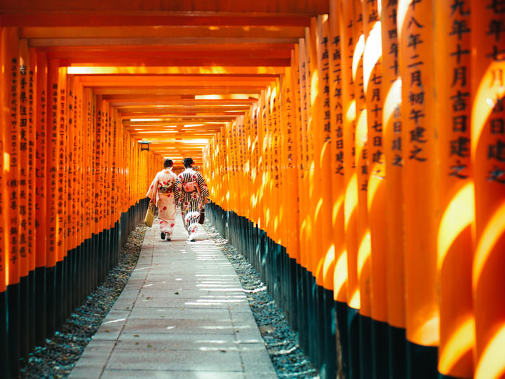Two women in kimonos walking through orange torii gate path at Fushimi Inari