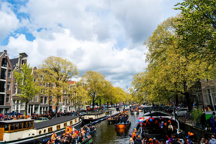 Amsterdam canal with tourist boats and lined with trees on partly cloudy day