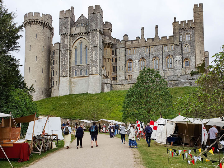 Medieval grey stone castle of Arundel with tents in front garden