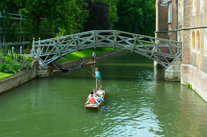 Student punting boat on Cambridge river under bridge