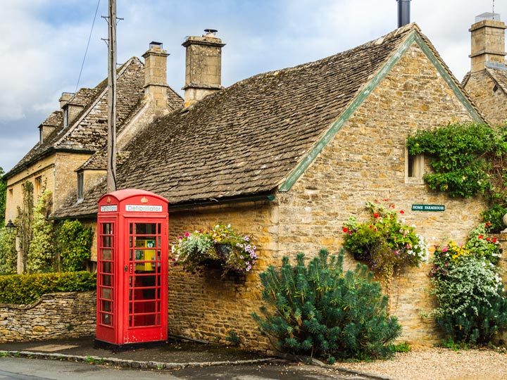 Cotswolds stone cottage with bushes and red phonebox out front
