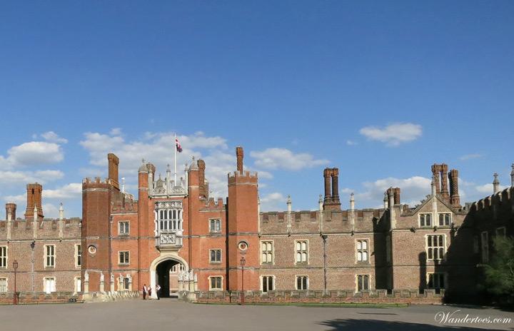 Stone facade of Hampton Court Palace on sunny day