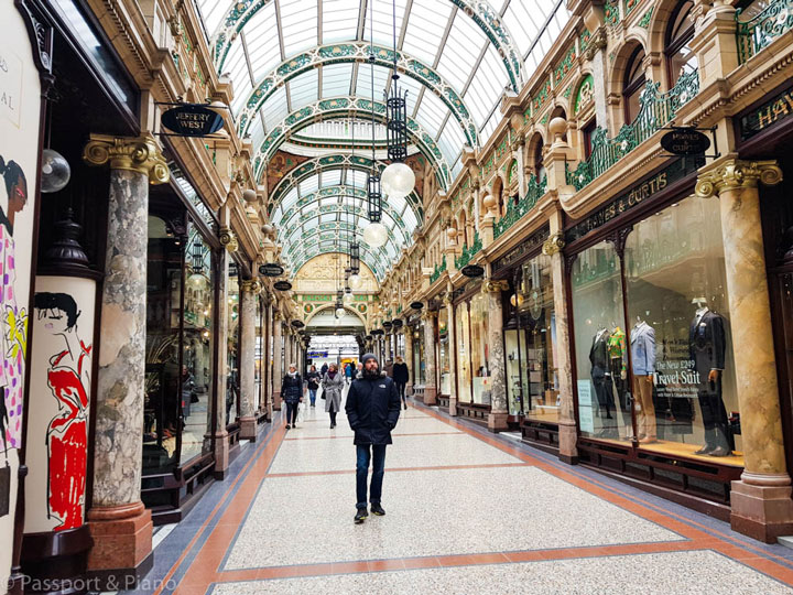 Man standing in covered Leeds shopping arcade with glass ceiling
