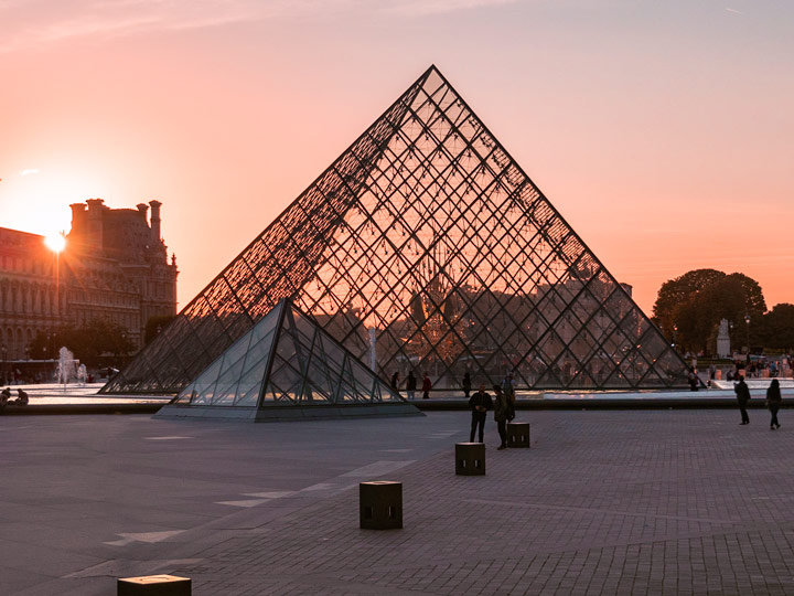 Louvre Pyramid with orange sunset in background