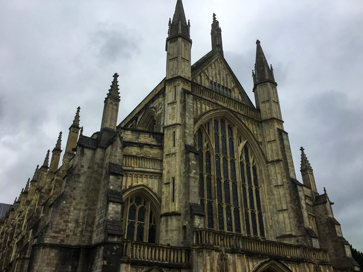 Front of Winchester Cathedral with arched windows and spires on cloudy day