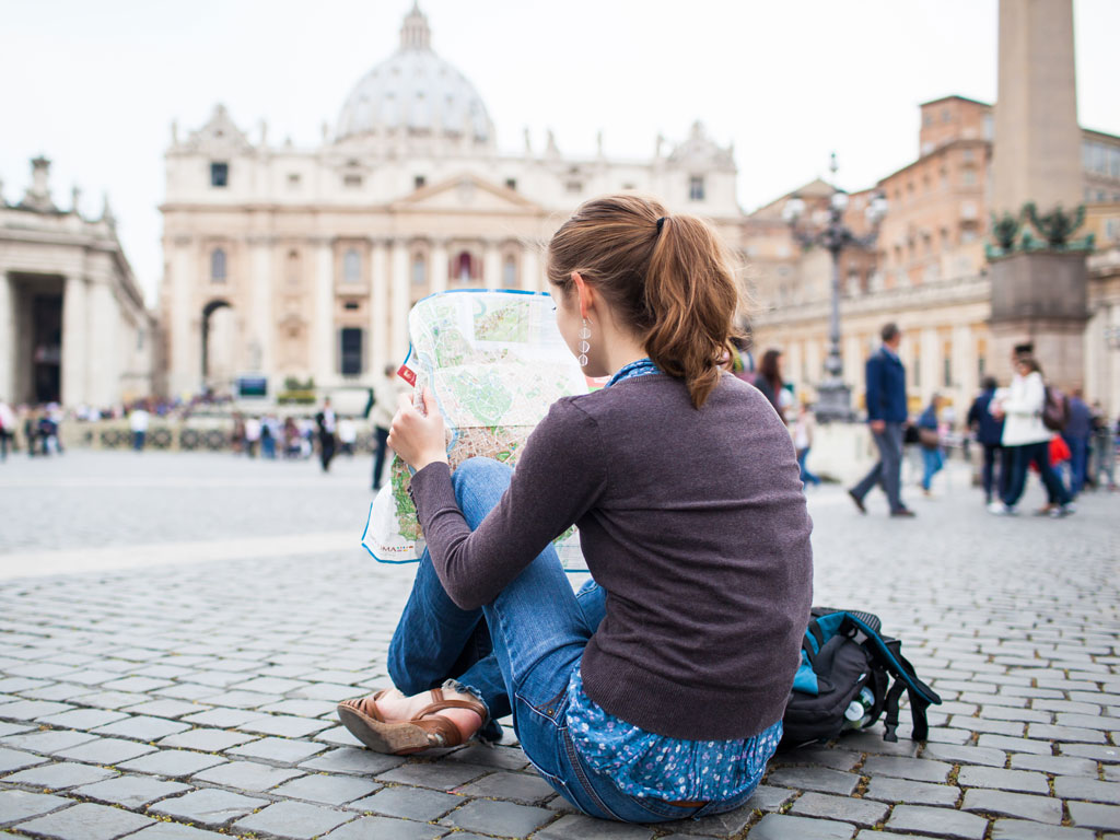 Expat or immigrant woman sitting on ground of busy plaza reading map.