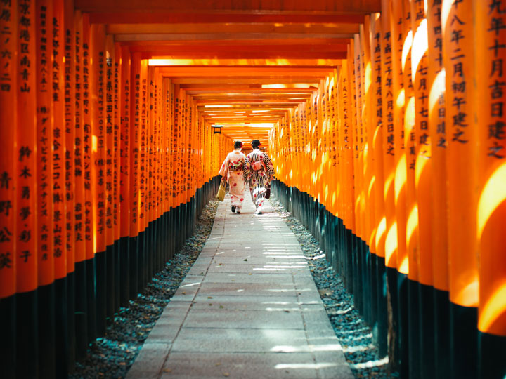 Two women in yukata walking through Fushimi Inari orange torii gates, the most famous things in Japan