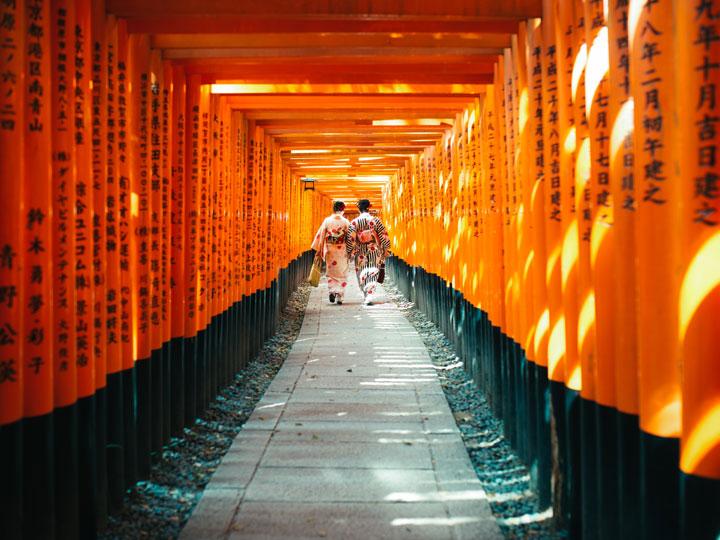 Two women in yukata walking through Fushimi Inari orange torii gates, the most famous things in Japan