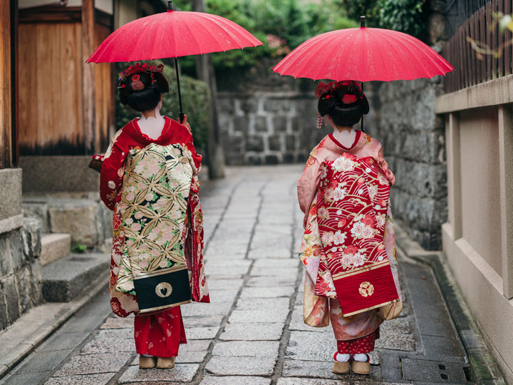 A geisha and maiko walking down street with red umbrellas