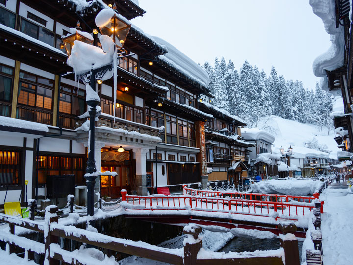 Ginzan Onsen with buildings and red bridge covered in snow