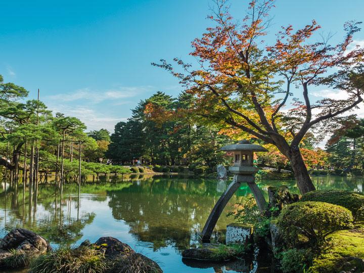 Kenrokuen Garden in Kanazawa Japan with pond, moss rocks, and autumn tree