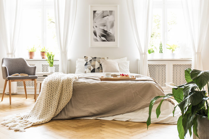 Brightly lit bedroom with white bed, grey chair, and green plant
