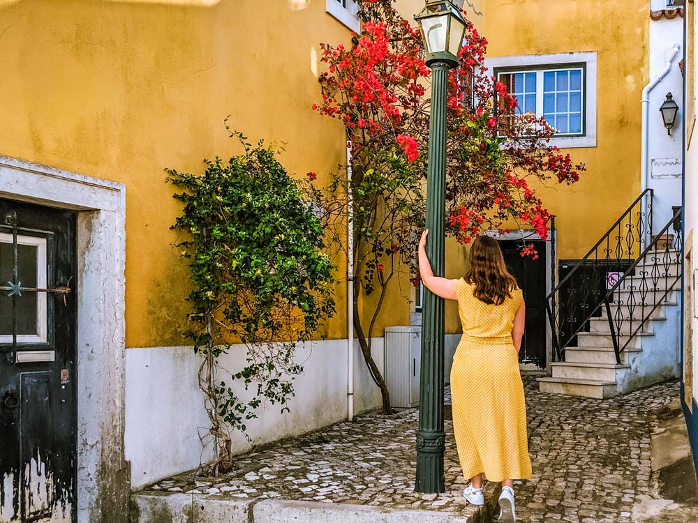 Girl in yellow dress by lamppost and yellow wall
