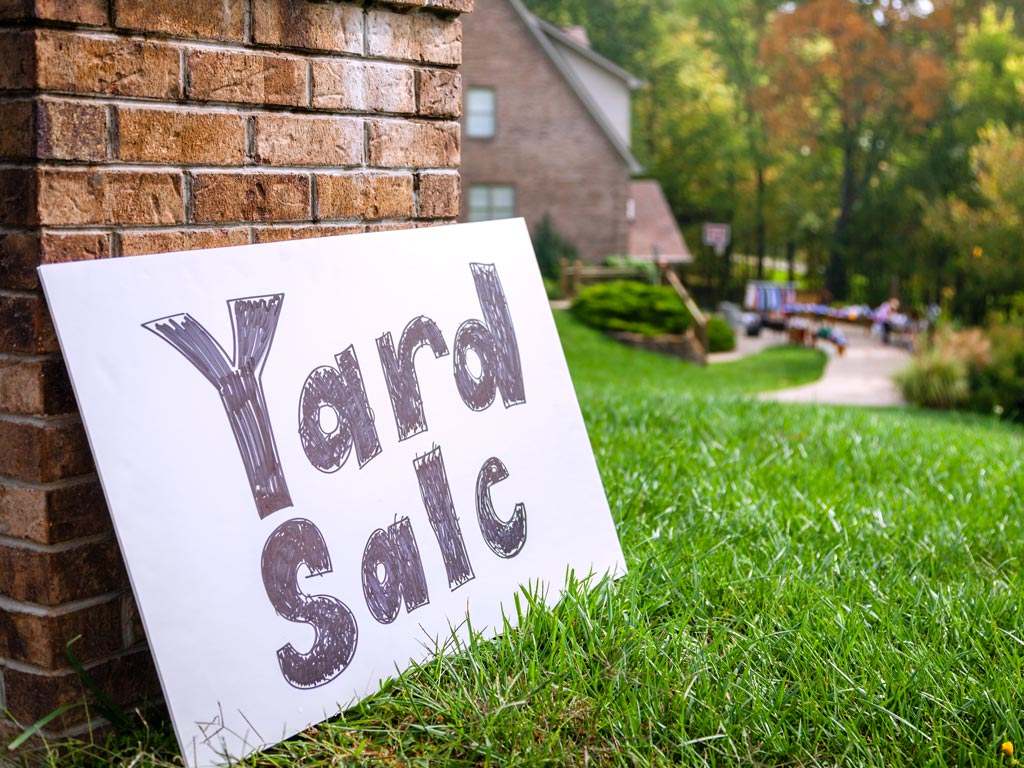 Yard sale sign sitting on grass in front of brick home.