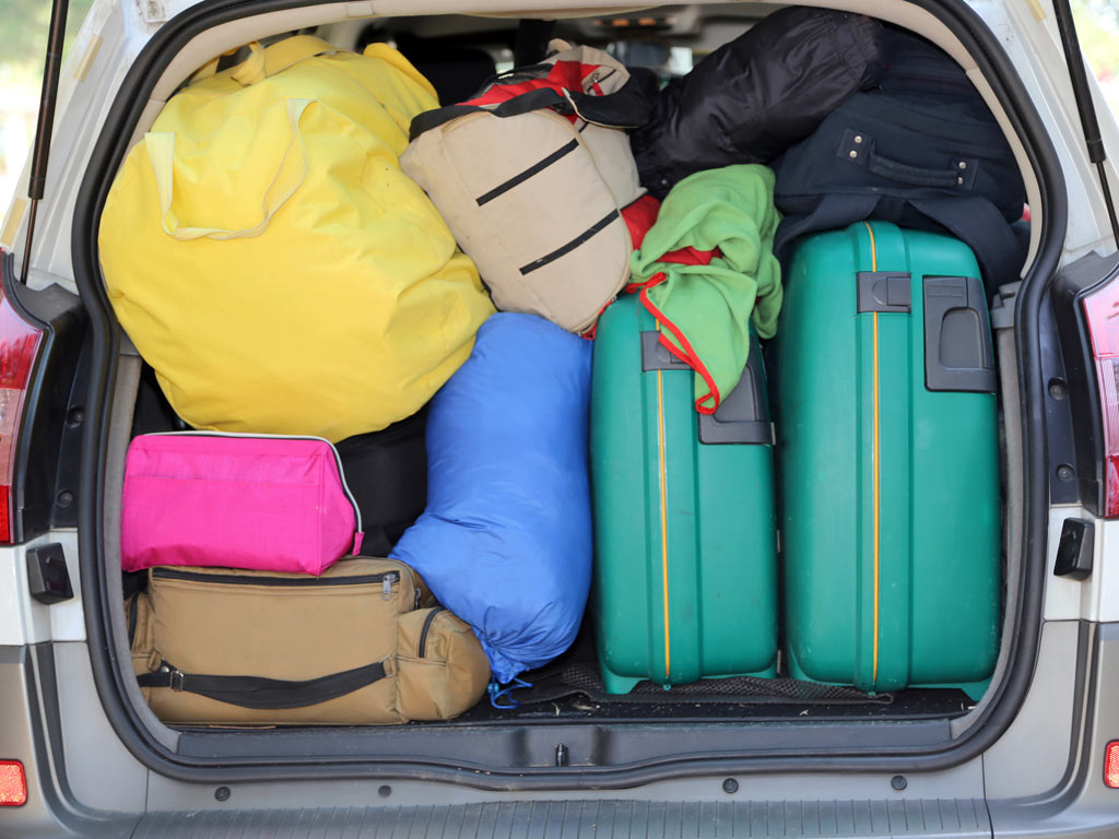 Car trunk packed with colorful luggage for moving abroad cheaply.