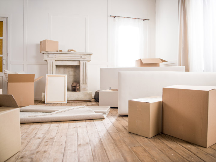 Living room with hardwood floors and white walls, and cardboard boxes on floor for moving out of the US
