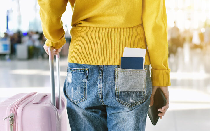 Girl in yellow sweater with pink suitcase at airport after learning how to move out of America