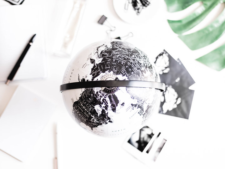 Overhead view of black and white globe, with photos and papers on desk